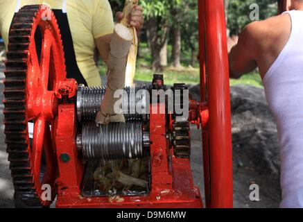 Two men operate a sugar cane press, squeezing out the juice from sugar canes in San Francisco de Paula, Cuba, 12 - Stock Photo