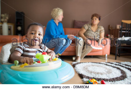Adopted baby boy with her mother in the background - Stock Photo