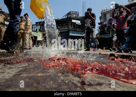 June 22, 2013 - Srinagar, Kashmir, India - Locals wash the blood stained road where two policemen were shot and - Stock Photo