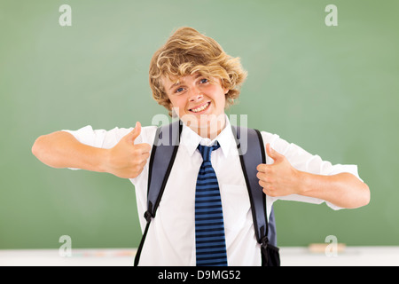 good looking young teenage boy thumbs up in classroom - Stock Photo