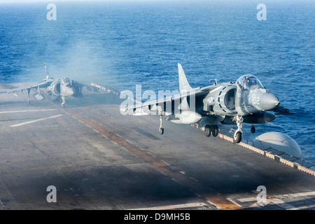US Marine Corps AV-8B Harrier fighter aircraft performs a vertical take off from the flight deck of the amphibious - Stock Photo
