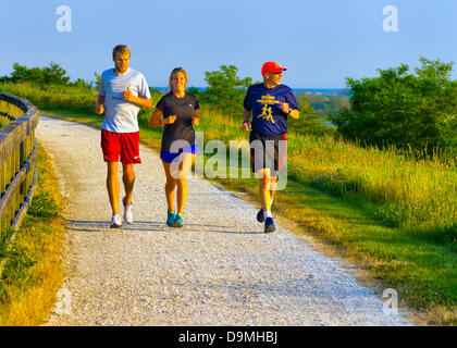 Merrick, New York, U.S. 20th June 2013. Three runners run on path around hill, at dusk on last full day of spring, - Stock Photo