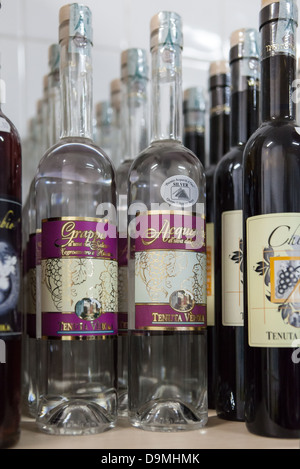 Bottles of wine and Grappa on the shelves of a factory outlet near Lecce, Italy. - Stock Photo