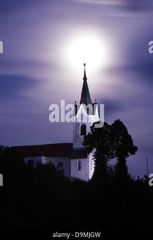 Slovenia. 22 June 2013. The 2013 supermoon rises over the spire of the church of Saint Marjeta (Sveta Marjeta) in - Stock Photo