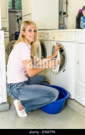 Woman filling a washing machine (model release) - Stock Photo