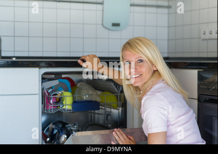 (Model release) Woman works in kitchen with a washer - Stock Photo