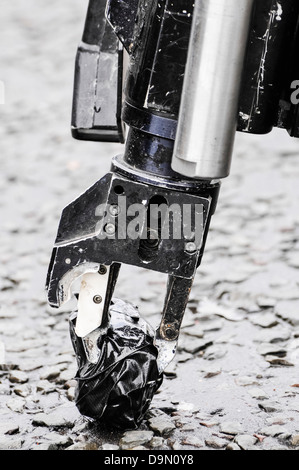 Pincer grip of an army bomb disposal robot picks up  a suspect object wrapped in tape - Stock Photo