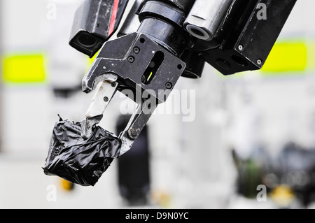 Pincer grip of an army bomb disposal robot holds a suspect object wrapped in tape - Stock Photo