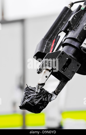 Pincer grip of an army 'Wheelbarrow' bomb disposal robot holds a suspect object wrapped in tape - Stock Photo
