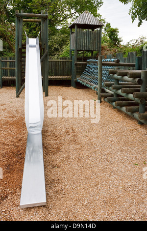 Adventure Play park for young children to enjoy with a slide, rope tunnel and castle turrets - Stock Photo