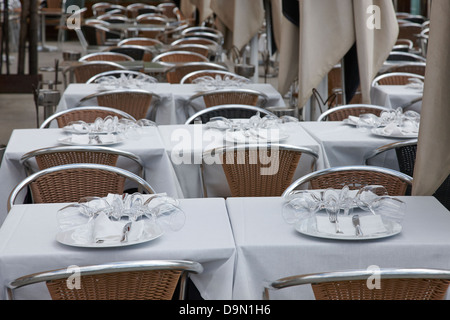 place settings on a table in an empty restaurant barcelona catalonia spain - Stock Photo