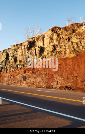 Road cut along highway 61 in northern Minnesota showing a basaltic lava flow on top of an underlying sedimentary - Stock Photo