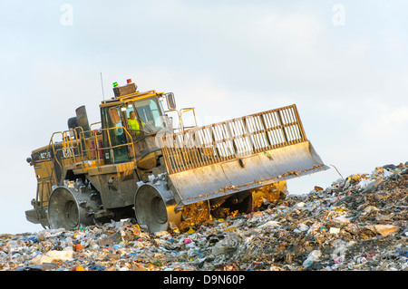 Heavy equipment compacting garbage at a sanitary landfill. - Stock Photo