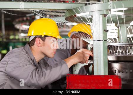 two textile weaving machine mechanics repairing loom - Stock Photo
