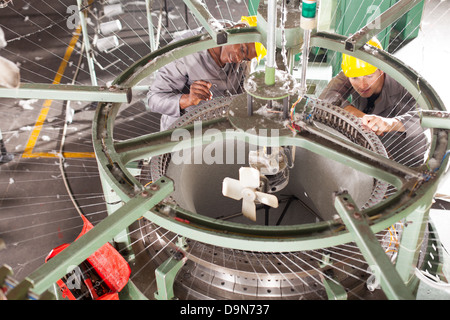 two textile factory technician repairing weaving loom - Stock Photo