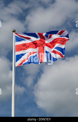 Union Jack Flag flying on Flagpole blowing in the wind. British Flag - Stock Photo