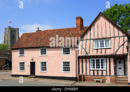 Pink timbered cottages and parish church of St Peter and St Paul's tall tower. Lavenham, Suffolk, England, UK, Britain - Stock Photo