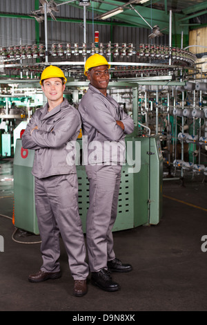 two industrial workers full length portrait in factory - Stock Photo