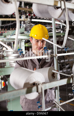 textile industrial worker working in factory - Stock Photo