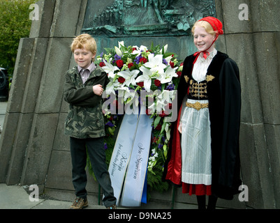 In Reykjavik, on Iceland's independence anniversary, two youngsters pose at a memorial--the girl in national dress - Stock Photo
