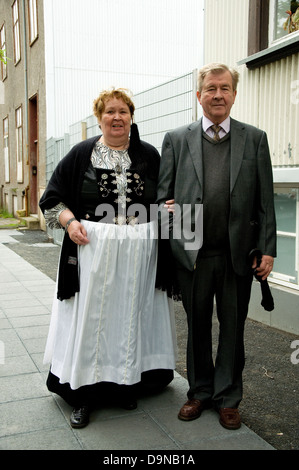On Iceland's National Day a middleaged couple--the woman wearing full national dress--walk in a Reyjkavik street - Stock Photo