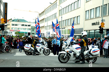 On Iceland's National Day police motorcyclists control traffic to allow a Scout parade to march in Reykjavik's city - Stock Photo
