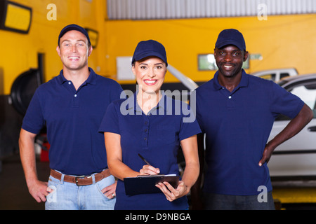group of happy workers in auto repair shop - Stock Photo