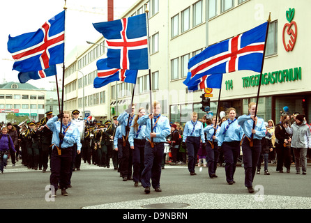 On Iceland's National Day a Scout group, male and female, marches in central Reykjavik, holding national flags - Stock Photo