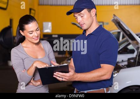auto mechanic and female customer in garage - Stock Photo