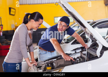 friendly mechanic showing female customer her car problem in garage - Stock Photo