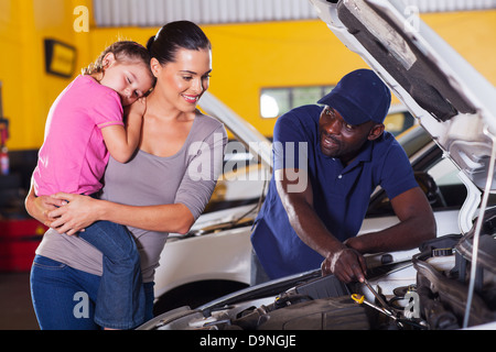 young mother taking her car for repair in garage with daughter sleeping on her shoulder - Stock Photo
