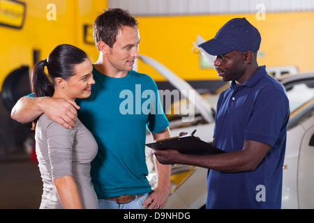 auto mechanic talking to young couple in repair shop - Stock Photo