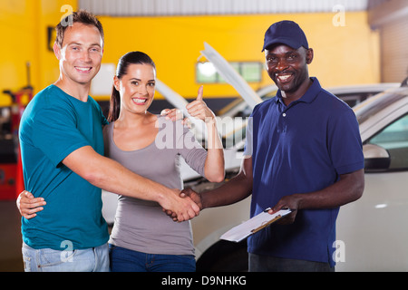 happy young couple giving thumb up to auto repair shop - Stock Photo