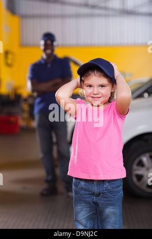 cute little girl wearing auto mechanic's cap in repair shop - Stock Photo