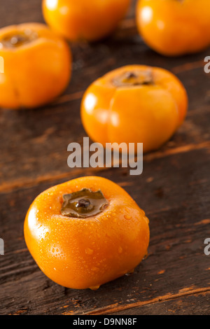 Organic Orange Persimmon Fruit against a background - Stock Photo