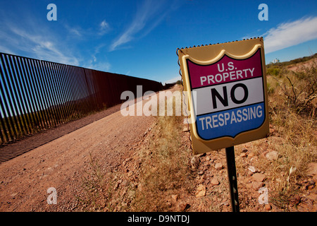 US property sign at US-Mexico border fence. - Stock Photo