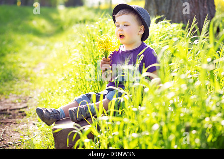 Cute little man sitting on the huge suitcase - Stock Photo