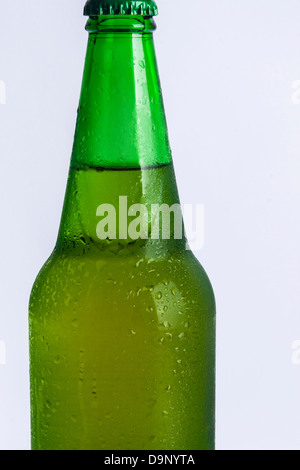 Wet bottle with cold beer on white background. - Stock Photo