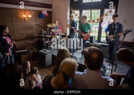 A teenage 4-piece band of drums, bass and two lead guitars perform in front of parents in an upstairs pub room in - Stock Photo