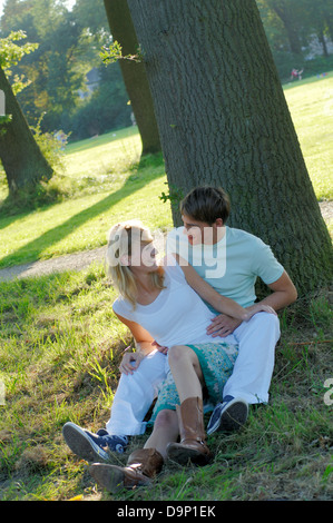 Young couple lying under trees - Stock Photo
