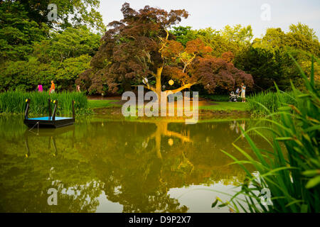 Old Westbury, New York, U.S. 22nd June 2013. Visitors stroll by the pond at dusk, at the Midsummer Night event at - Stock Photo