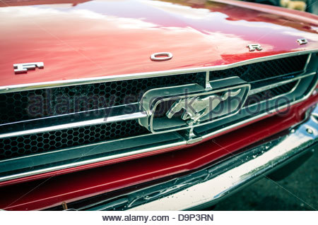 Ford logo and Mustang emblem on the front grille of a red 1965 First Generation Ford Mustang Coupe - Stock Photo