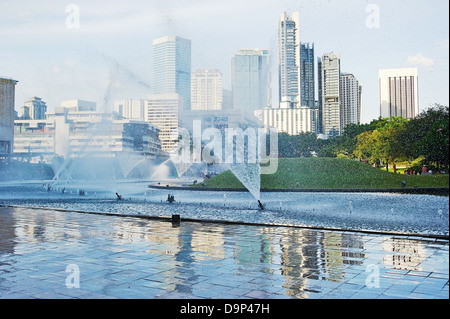 Central park in Kuala Lumpur, fountains in front of Petronas Twin Towers - Stock Photo