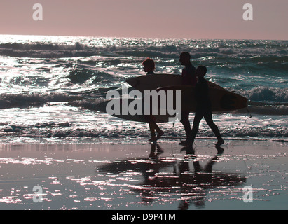 Three surfers, A father and two sons walking along the beach at sunset, Bude, Cornwall, UK 2013 - Stock Photo