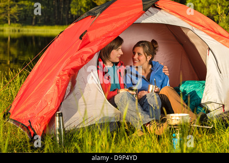 Happy camping teenagers sitting and embracing in tent - Stock Photo