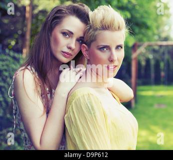 Two attractive ladies posing in the garden - Stock Photo