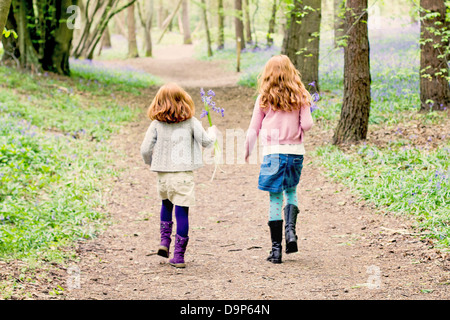 Two little girls walking through bluebell woods. - Stock Photo