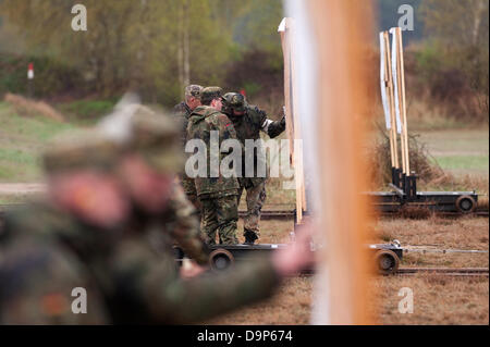 Members of an reservist company of teh German Armed Forces exercise on a shooting range and talk about the skrikes - Stock Photo