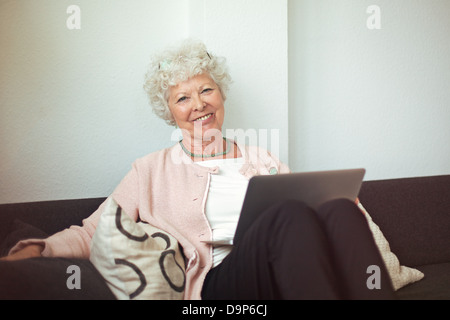 Happy senior woman sitting on the couch at home with laptop - Stock Photo