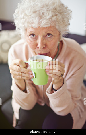 Closeup of a mature lady looking at you while drinking her tea - Stock Photo